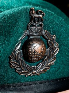 "The beret badge of the Royal Marines. The badge of the Royal Marines is designed to commemorate the history of the Corps. The Lion and Crown denotes a Royal regiment. King George III conferred this honour in 1802 ""in consideration of the very meritorious services of the Marines in the late war"". The ""Great Globe"", itself surrounded by laurels, was chosen by King George IV as a symbol of the Marines' successes in every quarter of the world. The laurels are believed to honour the gallantry they displayed during the investment and capture of Belle Isle, off Lorient, in April–June 1761."